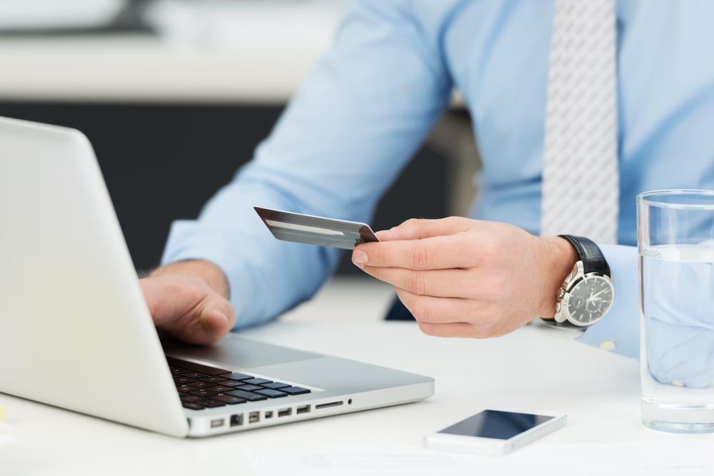 Businessman doing online banking, making a payment or purchasing goods on the internet entering his credit card details on a laptop, close up view of his hands