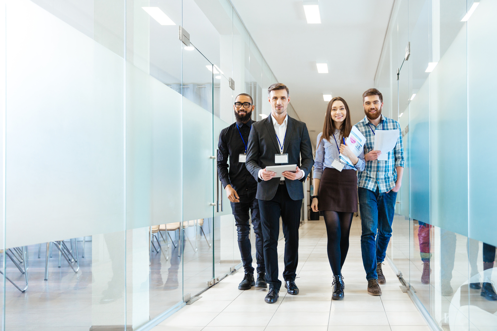 Full length of group of happy young business people walking the corridor in office together